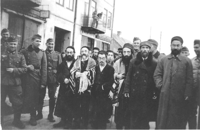 Smiling German soldiers surround a group of religious Jewish men on the street in Minsk